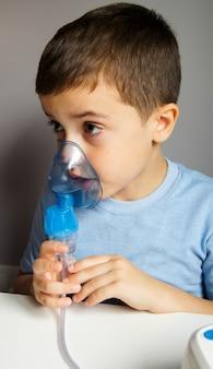 Garoto usando a máscara nebulizador e inalador para tratamento respiratório. conceito de cuidados de saúde e medicina.