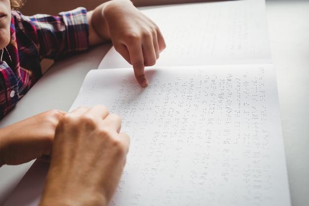 Garoto usando braille para ler
