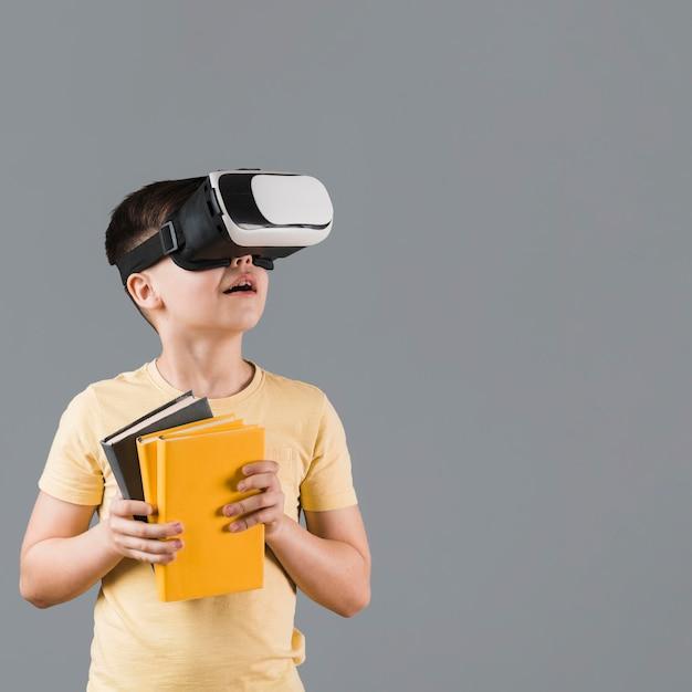 Garoto usando fone de ouvido de realidade virtual enquanto segura livros