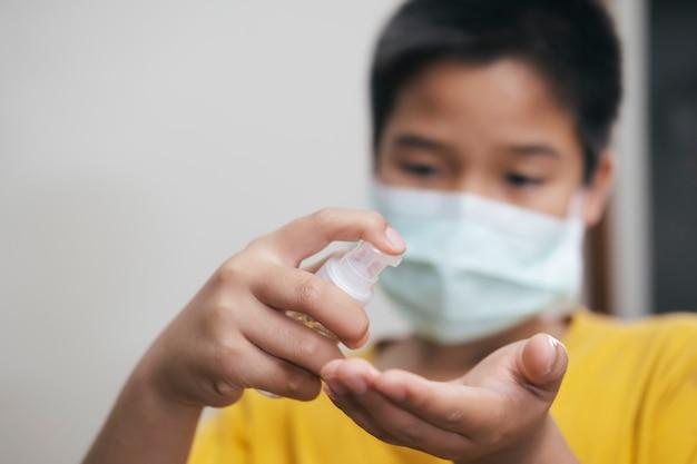 Garoto usando garrafa de dispensador de gel desinfetante para as mãos contra o coronavírus.
