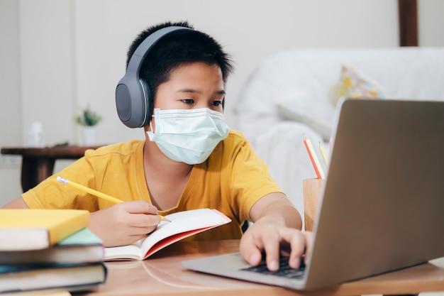 Garoto usando máscaras de rosto estudo on-line em casa.