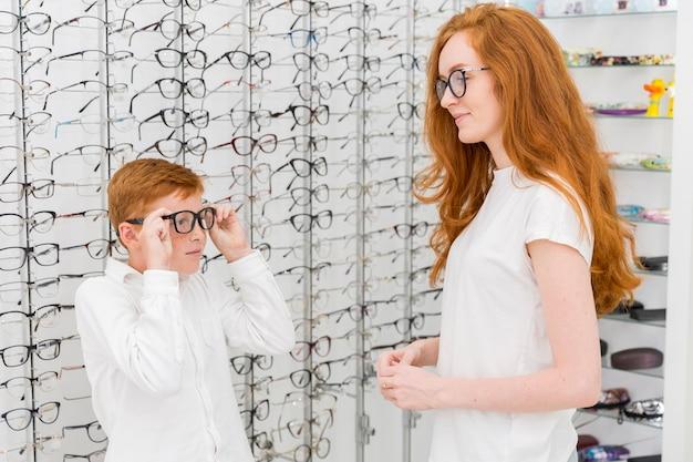 Garoto usando óculos na frente de sua jovem irmã na loja de óptica
