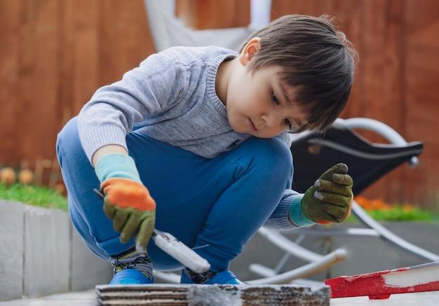 Garoto usando pincel pintura com cor cinza na caixa de papelão, little boy reciclagem ou papelão diy para seu brinquedo