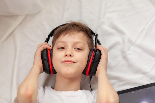 Garoto usando tablet digital e laptop ouvindo música no tapete em casa. educação on-line do conceito