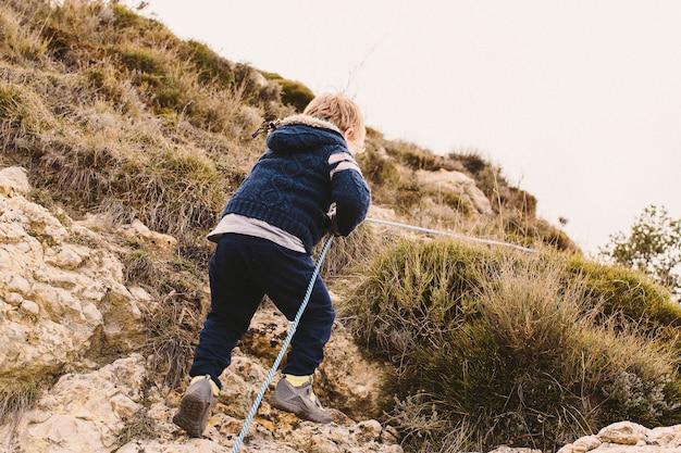 Garoto usando uma corda para escalar uma pequena montanha