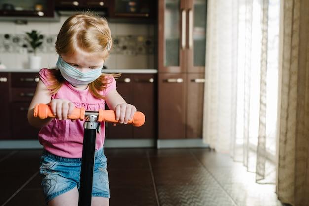 Garoto usando uma máscara. criança feliz brincando na cozinha durante a quarentena de covid-19.