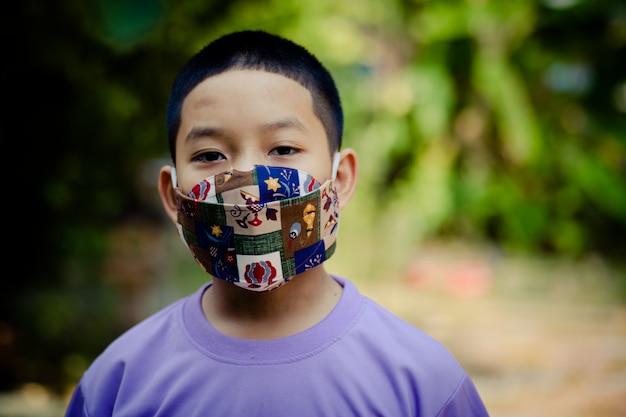 Garoto usando uma máscara para se proteger do vírus covid-19.