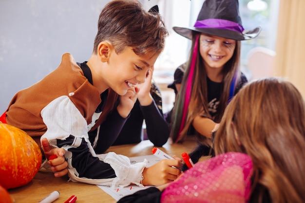 Garoto útil. menino de cabelos escuros vestindo uma fantasia de esqueleto de halloween ajudando sua irmã a colorir imagens na festa