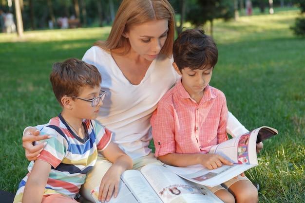 Garotos bonitos lendo um livro no parque durante uma aula ao ar livre com a professora