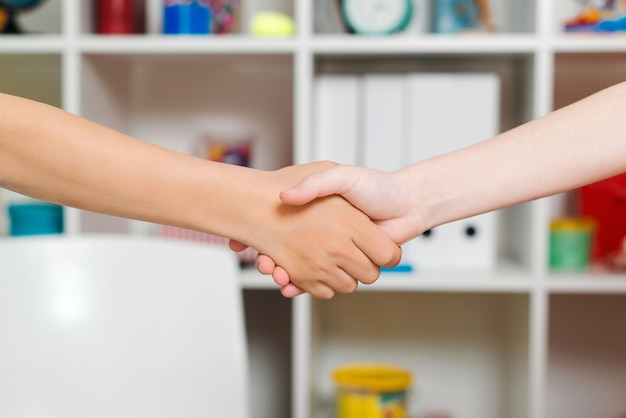 Garotos felizes, apertando as mãos e segurando as mãos uns dos outros.