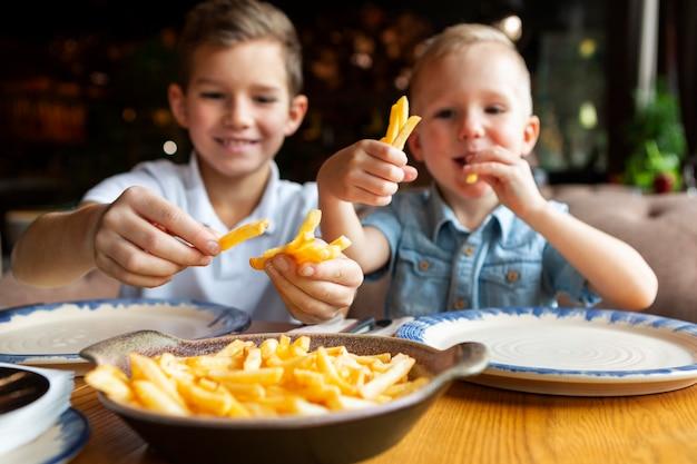 Garotos sorridentes de tiro médio comendo batatas fritas