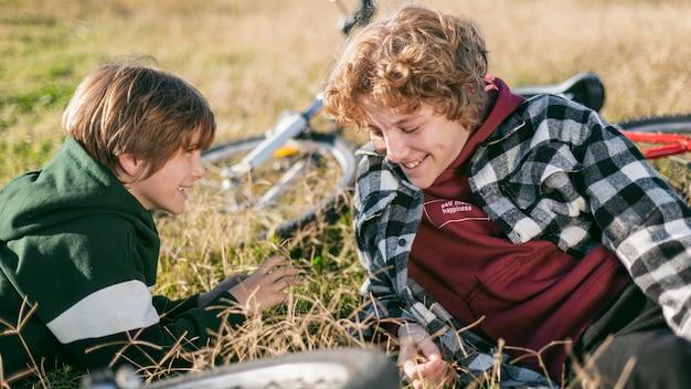 Garotos sorridentes relaxando na grama enquanto andam de bicicleta