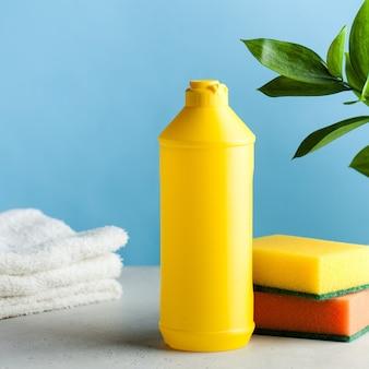 Garrafa amarela com lugar para logotipo, texto com detergente para louças, esponjas em uma superfície azul