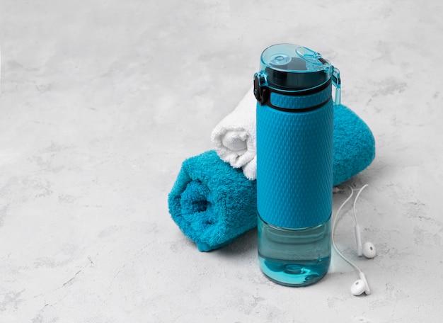 Garrafa azul de água e toalhas. equipamento desportivo na mesa de concreto cinza