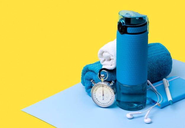 Garrafa azul de água, toalhas, fones de ouvido, cronômetro e bloco de notas. equipamento desportivo na mesa criativa
