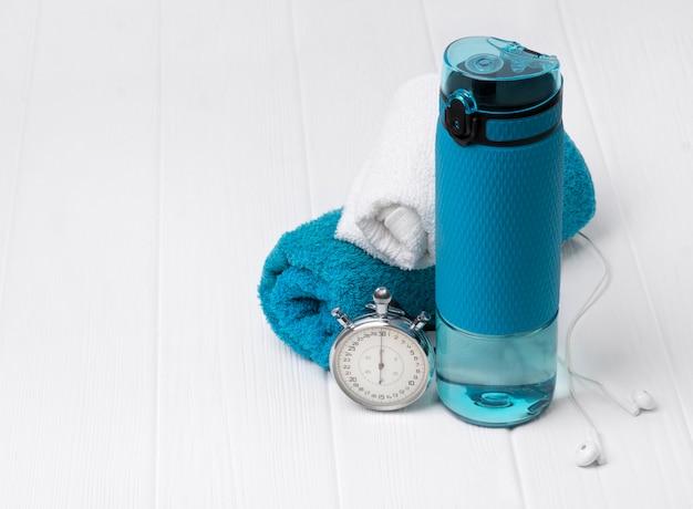 Garrafa azul de água, toalhas, fones de ouvido e cronômetro. equipamento desportivo na mesa de madeira branca