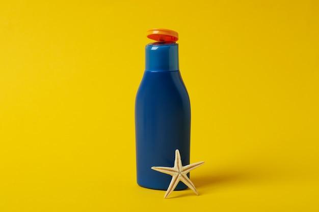 Garrafa azul de protetor solar e estrela do mar em fundo amarelo isolado