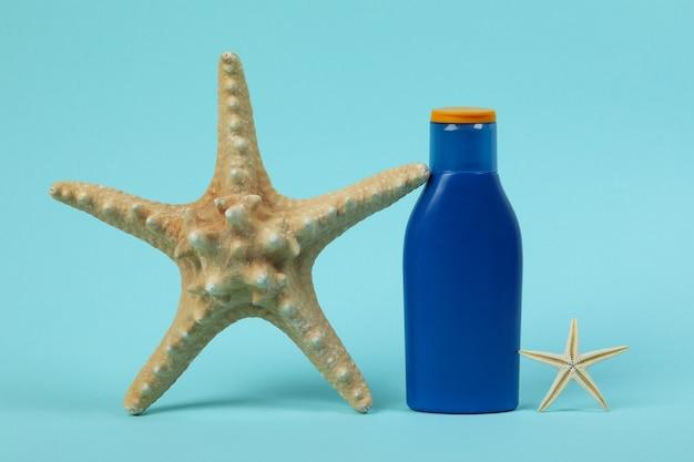 Garrafa azul de protetor solar e estrelas do mar em fundo azul isolado