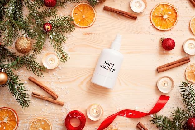 Garrafa branca de desinfetante para as mãos na mesa de madeira com diferentes decorações de natal