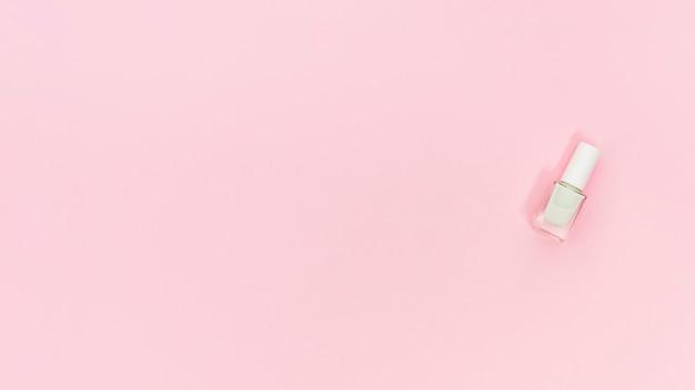 Garrafa branca de unha polonês em fundo rosa com espaço de cópia para escrever o texto