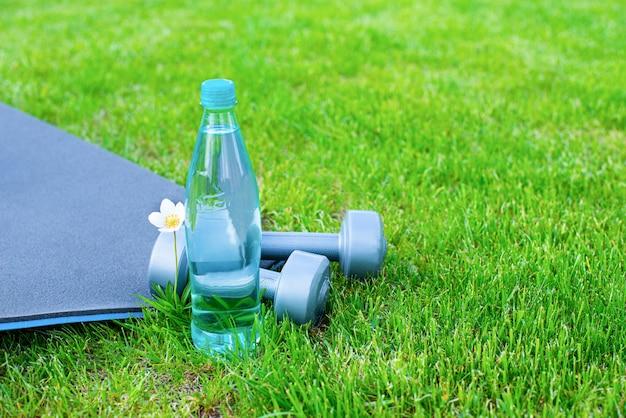 Garrafa com água, halteres e um tapete para esportes e yoga na grama verde. copie o espaço