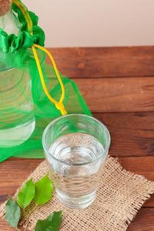 Garrafa com água limpa e as folhas verdes fechar