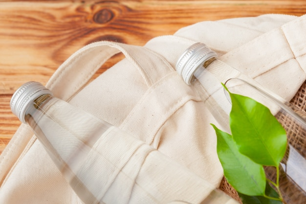 Garrafa com água limpa e as folhas verdes