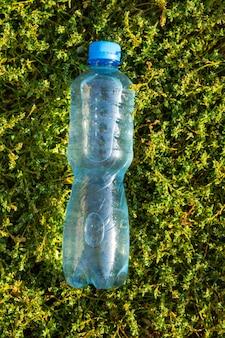 Garrafa com água limpa e fresca na grama verde. vista superior, copie o espaço