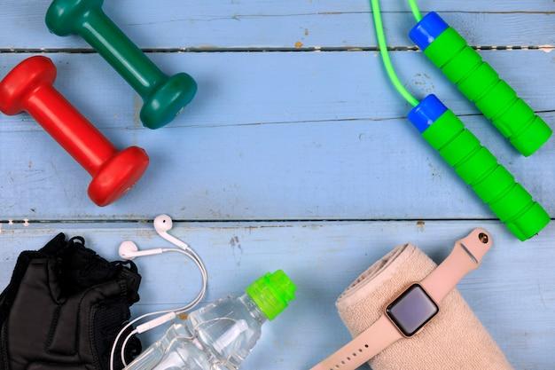 Garrafa com água, relógio inteligente, fones de ouvido e pular corda. copyspace