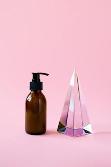 Garrafa com bomba para maquete de produto de beleza e prisma de pirâmide de vidro em fundo rosa