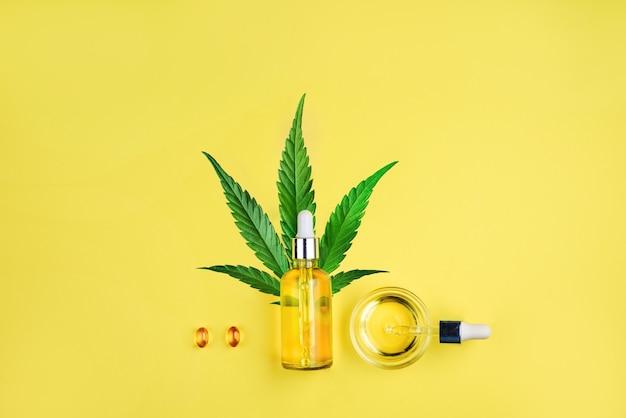 Garrafa com cápsulas de pipeta de óleo cbd e folha de cannabis em um fundo amarelo minimalismo flat lay