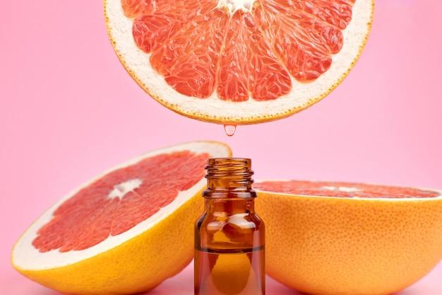 Garrafa com óleo cítrico essencial e toranjas vermelhas frescas