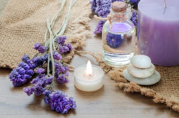 Garrafa com óleo essencial de lavanda, vela na mesa de madeira.