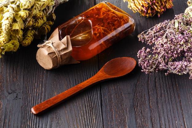 Garrafa com óleo vegetal com ervas na mesa rústica de madeira