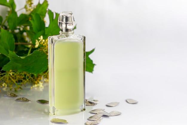 Garrafa com perfume masculino. rodeado por objetos brilhantes e folhas verdes em um fundo branco.