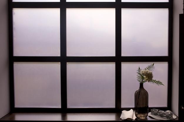 Garrafa com um raminho no peitoril da janela com vidro fosco branco.