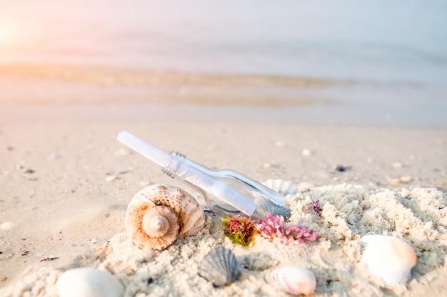 Garrafa com uma mensagem ou carta na praia perto da concha do mar. sos. copyspace.