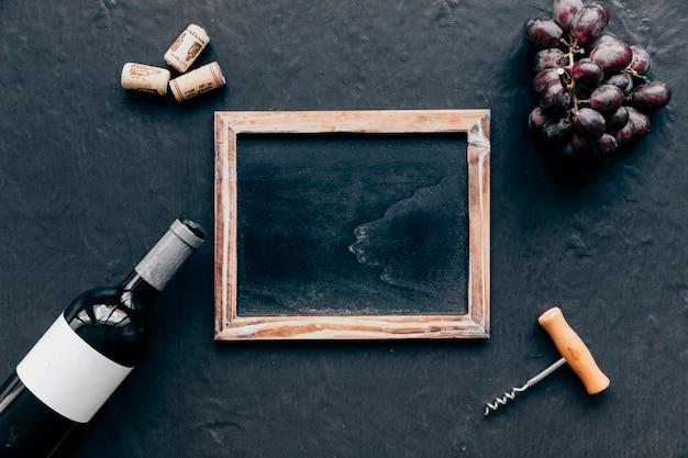 Garrafa com uva e saca-rolhas em volta do quadro-negro