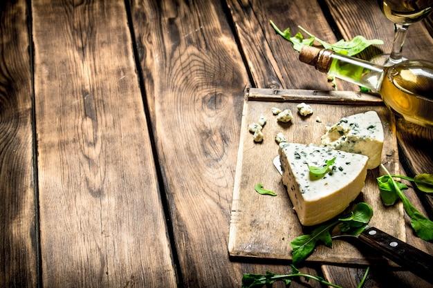 Garrafa com vinho branco e queijo azul em uma placa de corte.