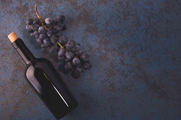 Garrafa com vinho tinto, cortiça e uvas.