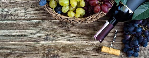 Garrafa com vinho tinto, saca-rolhas, uvas azuis na cesta, folhas sobre uma mesa de madeira.