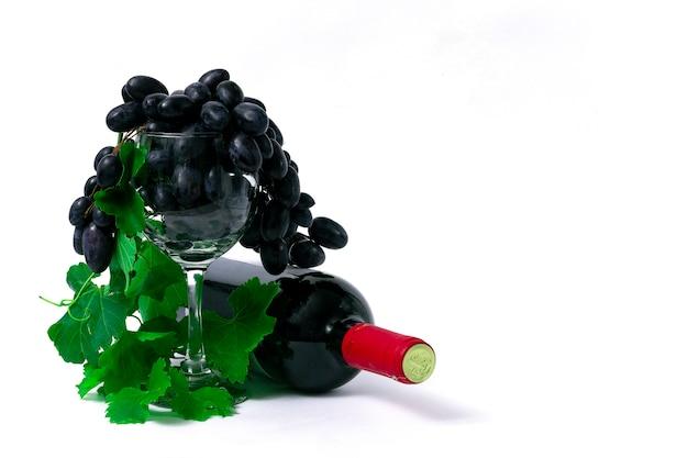 Garrafa com vinho tinto, taça de vinho com uvas