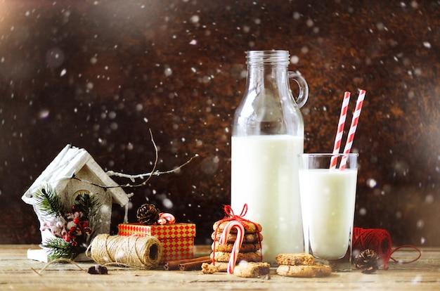 Garrafa, copo com leite para o papai noel, cookies, corda vermelha, estrelas de anis, paus de canela, cones, decoração