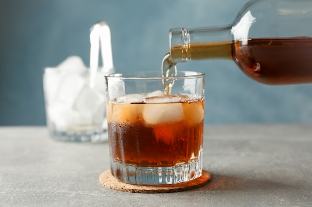Garrafa, copo de uísque e cubos de gelo no fundo cinza, close-up