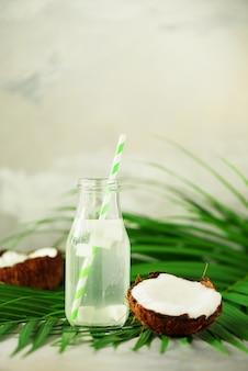 Garrafa da água do coco e frutos maduros frescos no fundo concreto cinzento. conceito de comida de verão. vegetariana, vegan, bebida de desintoxicação. suco de coco com palha em folhas de palmeira