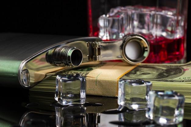 Garrafa de aço inoxidável álcool licor e gelo na mesa com vidro na nota do dólar