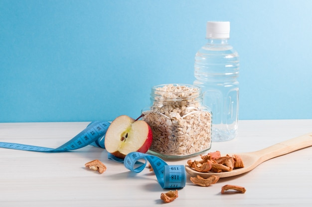 Garrafa de água, anka com aveia, colher grande de denrevy com maçãs secas, maçã cortada e fita métrica azul sobre a mesa