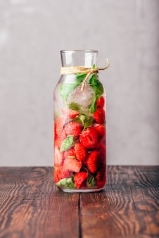 Garrafa de água aromatizada com folhas frescas de morango e manjericão
