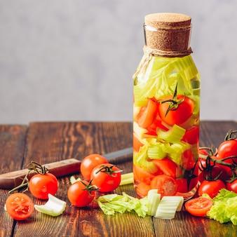 Garrafa de água aromatizada com legumes: tomate cereja e talos de aipo. ingredientes e faca na mesa de madeira. copie o espaço.