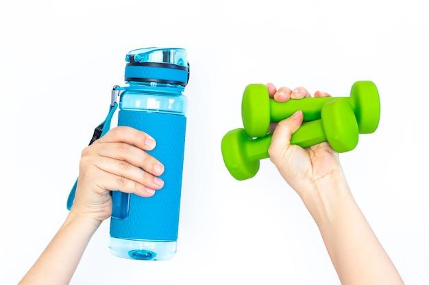 Garrafa de água azul de esportes e dois halteres verdes na mão de uma mulher isolado. equipamento desportivo conceito de fitness estilo de vida saudável